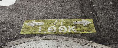 Street sign. Yellow-ish and graphic signs on the asphalt to warn pedestrians to look right and left before crossing the street royalty free stock images