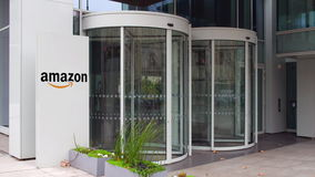 Street signage board with Amazon. com logo. Modern office building. Editorial 4K 3D rendering