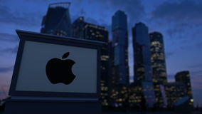 Street signage board with Apple Inc. logo in the evening. Blurred business district skyscrapers background. Editorial 4K. Clip ProRes stock video footage
