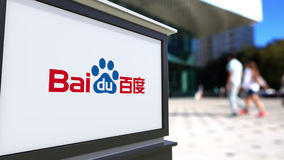 Street signage board with Baidu logo. Blurred office center and walking people background. Editorial 3D rendering Stock Photo