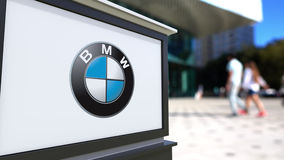 Street signage board with BMW logo. Blurred office center and walking people background. Editorial 3D rendering Stock Photos