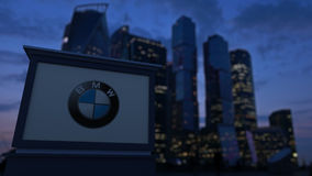 Street signage board with BMW logo in the evening. Blurred business district skyscrapers background. Editorial 3D Stock Photography
