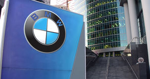 Street signage board with BMW logo. Modern office center skyscraper and stairs background. Editorial 3D rendering Stock Photo