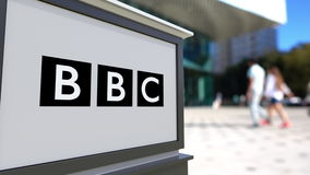 Street signage board with British Broadcasting Corporation BBC logo. Blurred office center and walking people background Stock Photo
