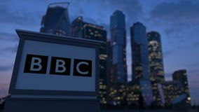 Street signage board with British Broadcasting Corporation BBC logo in the evening. Blurred business distric. T skyscrapers background. Editorial 3D rendering 4K stock video footage