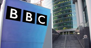 Street signage board with British Broadcasting Corporation BBC logo. Modern office center skyscraper and stairs. Background. Editorial 3D rendering 4K clip stock video