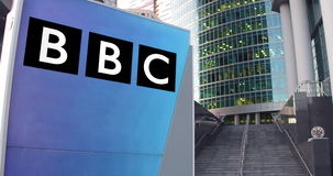 Street signage board with British Broadcasting Corporation BBC logo. Modern office center skyscraper and stairs Stock Photos