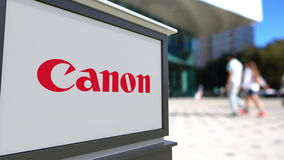 Street signage board with Canon Inc. logo. Blurred office center and walking people background. Editorial 3D rendering Stock Image