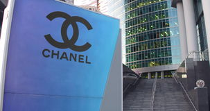 Street signage board with Chanel logo. Modern office center skyscraper and stairs background. Editorial 3D rendering Royalty Free Stock Image