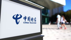 Street signage board with China Telecom logo. Blurred office center and walking people background. Editorial 4K 3D stock footage