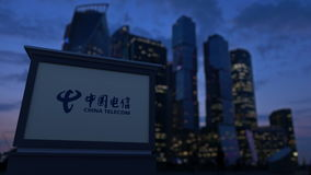 Street signage board with China Telecom logo in the evening. Blurred business district skyscrapers background. Editorial stock video footage