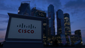 Street signage board with Cisco Systems logo in the evening. Blurred business district skyscrapers background. Editorial Stock Image