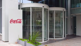 Street signage board with Coca-Cola logo. Modern office building. Editorial 3D rendering Royalty Free Stock Image