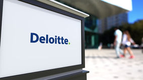 Street signage board with Deloitte logo. Blurred office center and walking people background. Editorial 3D rendering. United States Royalty Free Stock Photography