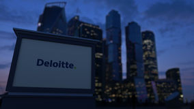Street signage board with Deloitte logo in the evening. Blurred business district skyscrapers background. Editorial 3D Royalty Free Stock Photo