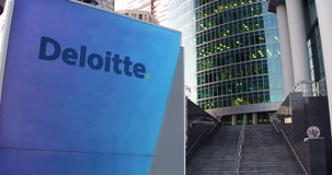 Street signage board with Deloitte logo. Modern office center skyscraper and stairs background. Editorial 3D rendering. United States Stock Image