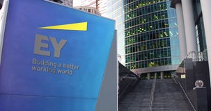 Street signage board with Ernst and Young logo. Modern office center skyscraper, stairs background. Editorial 3D. Street signage board with Ernst and Young logo Stock Image