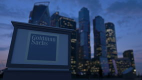 Street signage board with The Goldman Sachs Group, Inc. logo in the evening. Blurred business district skyscraper. S background. Editorial 3D rendering 4K clip stock footage