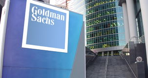 Street signage board with The Goldman Sachs Group, Inc. logo. Modern office center skyscraper and stairs background. Editorial 3D rendering 4K clip stock video