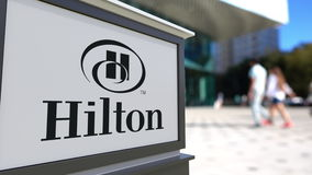 Street signage board with Hilton Hotels Resorts logo. Blurred office center and walking people background. Editorial 3D. United States Stock Image