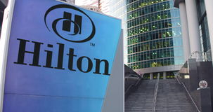 Street signage board with Hilton Hotels Resorts logo. Modern office center skyscraper and stairs background. Editorial Royalty Free Stock Photography