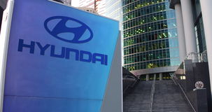 Street signage board with Hyundai Motor Company logo. Modern office center skyscraper and stairs background. Editorial