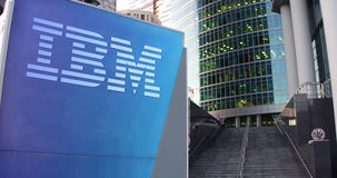 Street signage board with IBM logo. Modern office center skyscraper and stairs background. Editorial 3D rendering. United States Royalty Free Stock Image