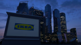 Street signage board with Ikea logo in the evening. Blurred business district skyscrapers background. Editorial 3D Stock Image