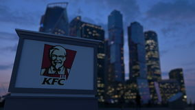 Street signage board with Kentucky Fried Chicken KFC logo in the evening.  Blurred business district skyscraper stock video footage