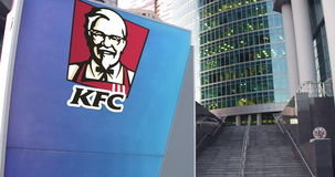 Street signage board with Kentucky Fried Chicken KFC logo. Modern office center skyscraper and stairs background Royalty Free Stock Images