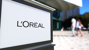 Street signage board with L`Oreal logo. Blurred office center and walking people background. Editorial 3D rendering Royalty Free Stock Images