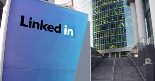 Street signage board with LinkedIn logo. Modern office center skyscraper and stairs background. Editorial 3D rendering Stock Images