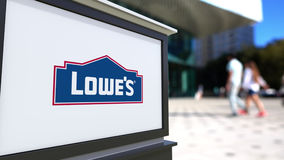 Street signage board with Lowe`s logo. Blurred office center and walking people background. Editorial 3D rendering Stock Image