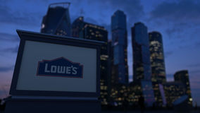 Street signage board with Lowe`s logo in the evening. Blurred business district skyscrapers background. Editorial 3D Royalty Free Stock Photography