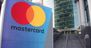 Street signage board with MasterCard logo. Modern office center skyscraper and stairs background. Editorial 3D rendering Stock Photos