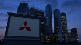 Street signage board with Mitsubishi logo in the evening. Blurred business district skyscrapers background. Editorial 3D Stock Image