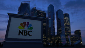 Street signage board with National Broadcasting Company NBC logo in the evening. Blurred business district skyscrapers Royalty Free Stock Images