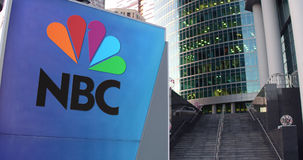 Street signage board with National Broadcasting Company NBC logo. Modern office center skyscraper and stairs background Stock Photography