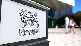 Street signage board with Nestle logo. Blurred office center and walking people background. Editorial 3D rendering Stock Image