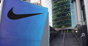 Street signage board with Nike logo. Modern office center skyscraper and  stairs background. Editorial