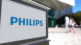 Street signage board with Philips logo. Blurred office center and walking people background. Editorial 3D rendering. Street signage board with Philips logo Stock Images