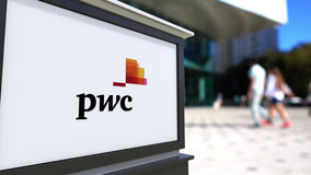 Street signage board with PricewaterhouseCoopers PwC logo. Blurred office center and walking people background Stock Images