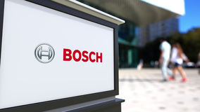Street signage board with Robert Bosch GmbH logo. Blurred office center and walking people background. Editorial 3D Stock Image