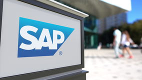 Street signage board with SAP SE logo. Blurred office center and walking people background. Editorial 3D rendering 4K
