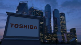 Street signage board with Toshiba Corporation logo in the evening.  Blurred business district skyscrapers backgroun Stock Photos
