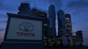 Street signage board with Toyota logo in the evening. Blurred business district skyscrapers background. Editorial 3D Stock Image
