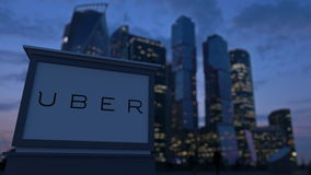 Street signage board with Uber Technologies Inc. logo in the evening. Blurred business district skyscrapers backgroun. D. Editorial 3D royalty free stock images