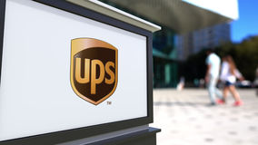 Street signage board with United Parcel Service UPS logo. Blurred office center and walking people background. Editorial Stock Image