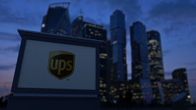 Street signage board with United Parcel Service UPS logo in the evening. Blurred business district skyscrapers Royalty Free Stock Images
