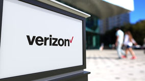 Street signage board with Verizon Communications logo. Blurred office center and walking people background. Editorial 3D royalty free illustration